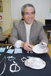 いかだで育てた淡水真珠を手に語る美島さん=脇田撮影