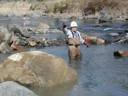 河川改修工事で石の配置を指示する福留脩文さん=高知県馬路村の安田川で10年1月、西日本科学技術研究所提供