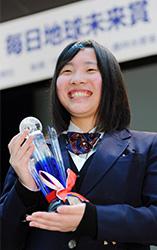 毎日地球未来賞のトロフィーを手に笑顔の佐々木愛さん