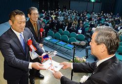 黒潮実感センターの神田優さんに賞金目録を手渡す久保俊裕・クボタ代表取締役副社長